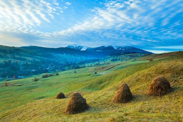 Туманный ранний рассвет осенью карпаты, украина (вдалеке говерла и гора петрос)