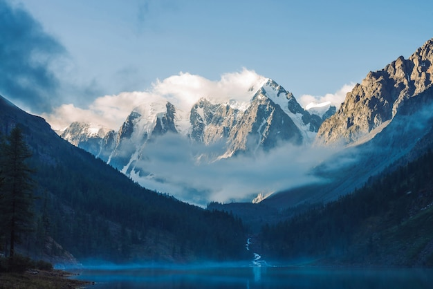 Туманный пейзаж с горным озером и туманом над водой