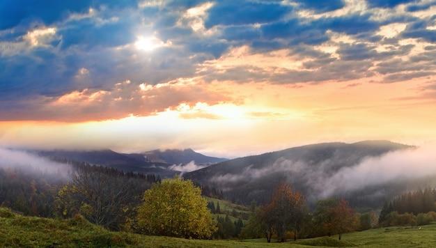 Misty morning and sunshine thru clouds in autumn carpathian mountain, ukraine. high resolution stitch panorama image.