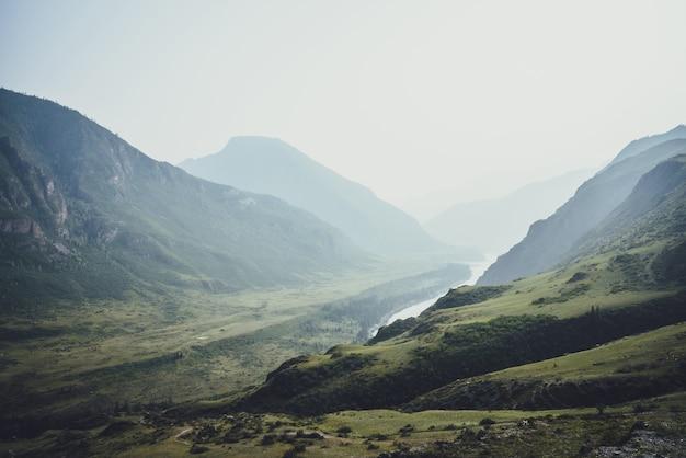 霧の中で広い山の川の背景に丘や岩と霧の山の風景。雨天時の濃い緑の谷に山の起伏と大きな川のある大気の風景。憂鬱な天気