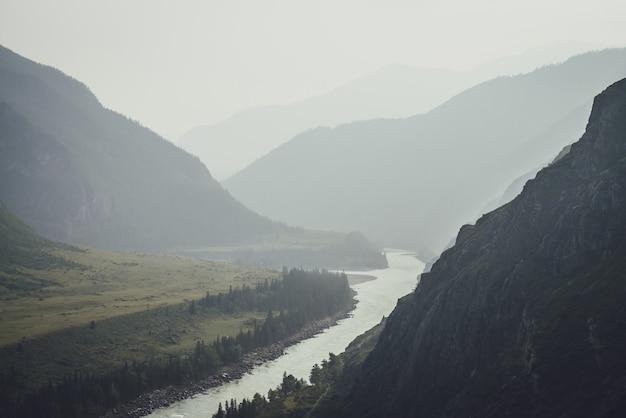 広い山川のある霧深い山の風景。霧の中で2つの山川の合流点と濃い緑色の暗い風景。雨天時の大河川の合流点への暗い大気の眺め。