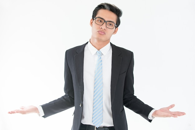 Misunderstanding asian businessman shrugging arms