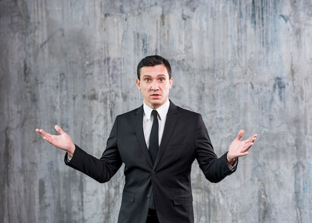Misunderstanding businessman standing with raised hands