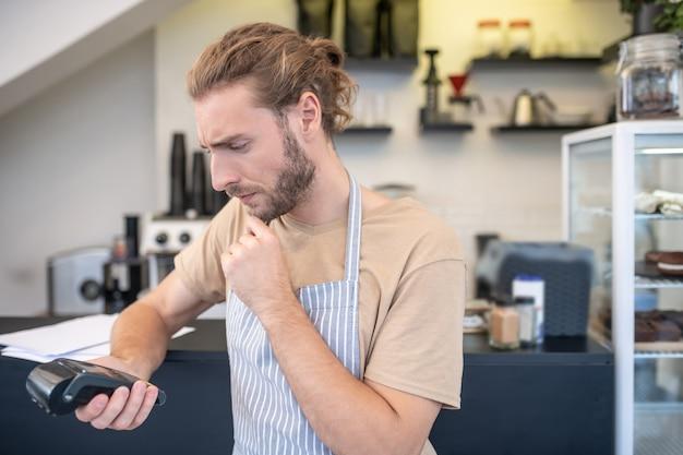 Недоразумение. обеспокоенный молодой бородатый мужчина в футболке и фартуке задумчиво смотрит на портативный терминал в руке в кафе
