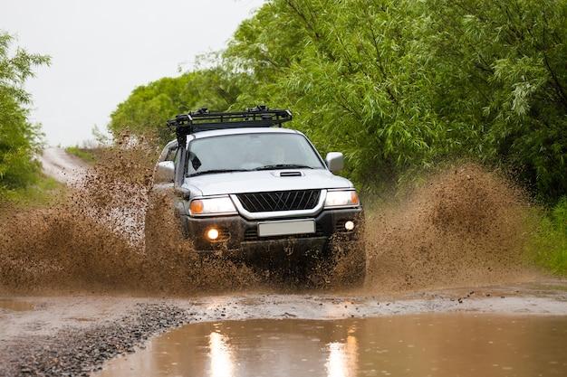 빗속에서 물살을 가르며 움직이는 미쓰비시 파제로 스포츠