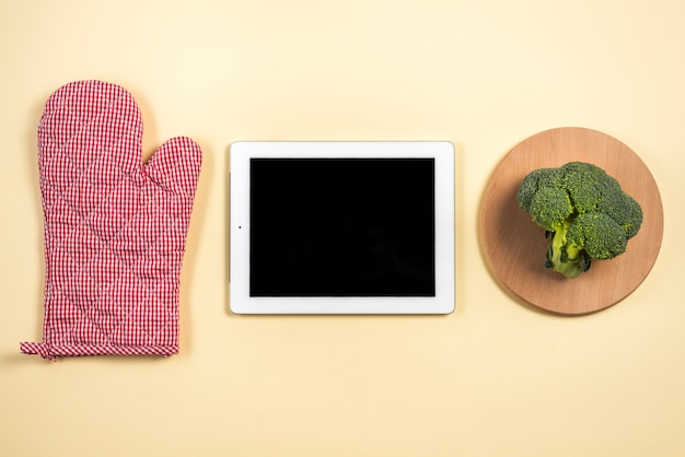 Mitt oven glove; digital tablet and broccoli on wooden tray against beige background