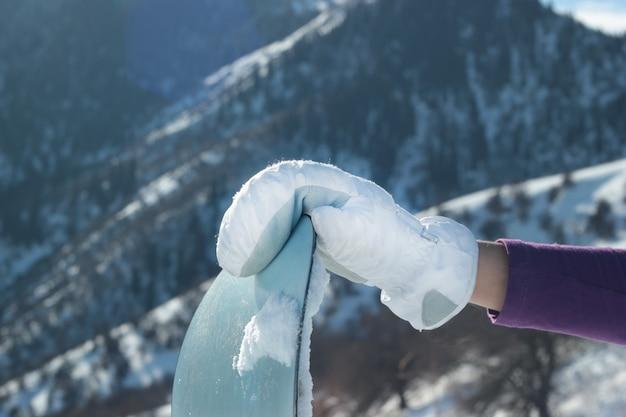 日光の下で雪に覆われた山々に対してスノーボードの鼻にミトングローブ