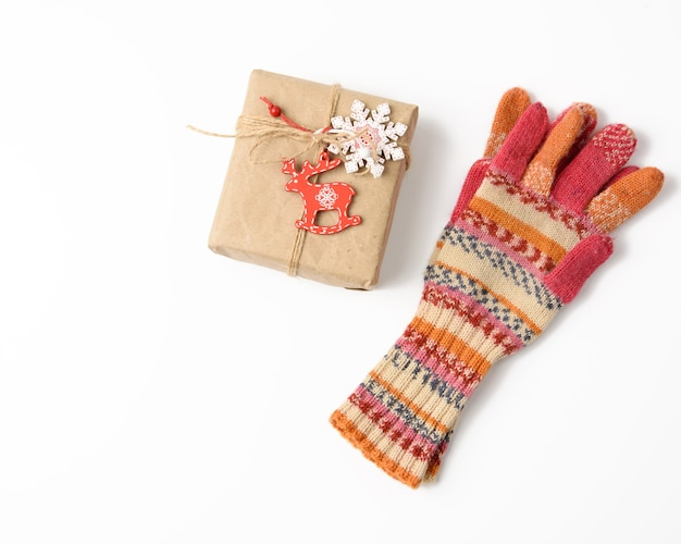 Mittens and box wrapped in brown kraft paper and tied with rope, gift on white surface