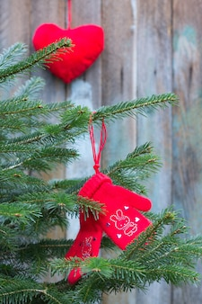 Mittens knitted from camel wool red color decorated with red rhinestones hearts bunnies on the branch of a christmas tree on a background of old boards and christmas toys in the shape of a heart