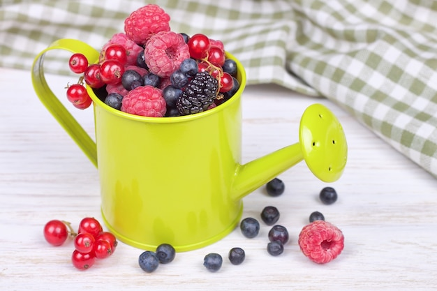 Mix of berries in a small light green decorative watering can on white wooden background. strawberry, raspberry, mulberry, red currant, blueberry