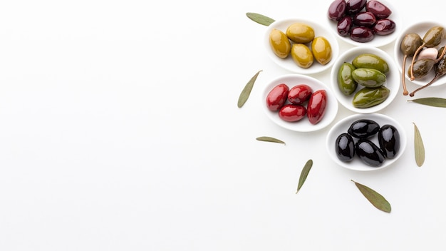 Mix of black red green purple yellow olives and oil with copy space