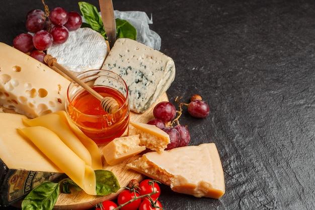 Смешайте сыр на темном фоне на деревянной доске с виноградом, медом, орехами, помидорами и базиликом. вид сверху.