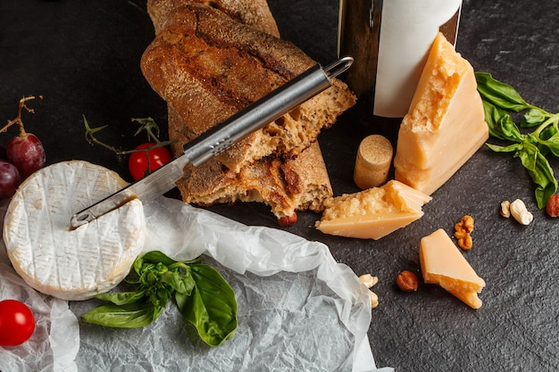 Смешайте сыр на темном фоне на деревянной доске с виноградом, медом, вином, хлебом, орехами, помидорами и базиликом. вид сверху.