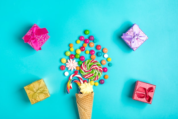 Mix colorful chocolate sweets spilled out of ice cream waffle cone, gift boxes on blue  flat lay