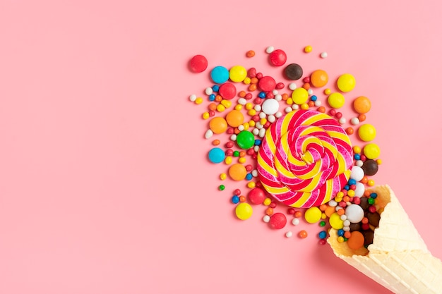 Mix colorful chocolate sweets spilled out of ice cream waffle cone on pink  flat lay