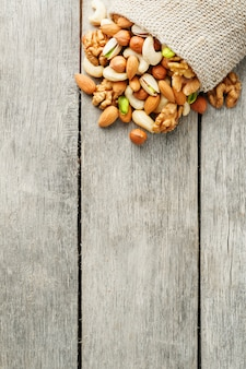 Mix of different nuts in a wooden cup against the background of fabric from burlap