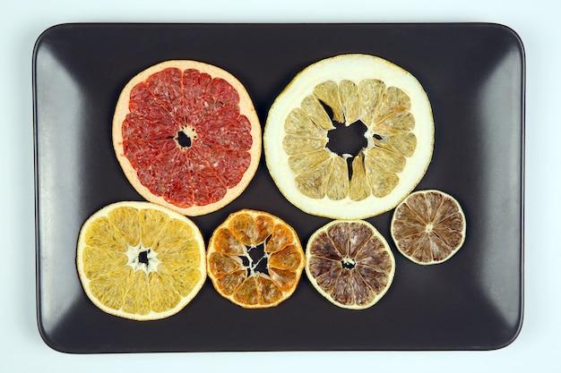 Смешайте на тарелке разные кусочки сушеных цитрусовых.