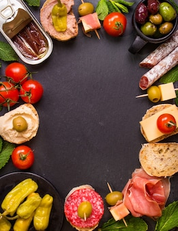 Mix of different snacks and appetizers. spanish tapas on a black stone background.
