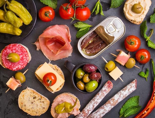 Mix of different snacks and appetizers. spanish tapas on a black stone plate.