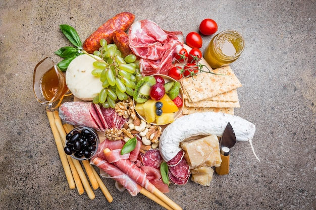 Mix of different snacks and appetizers. spanish tapas or italian wine set on a wooden plate