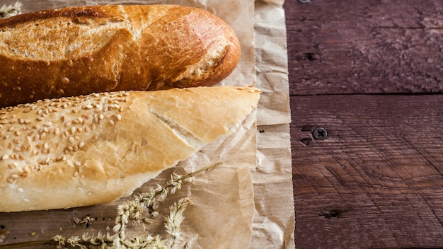 Mix of different varieties of bread lying on a wooden table