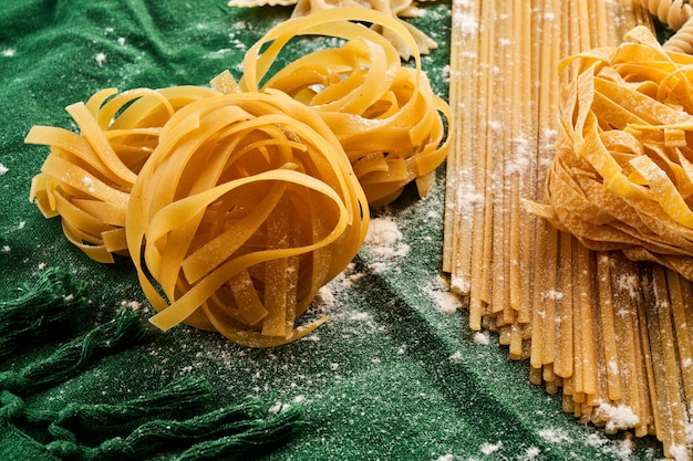 Mix of different varieties of pasta on green fabric background, cooking assorted macaroni concept