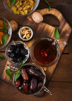 ドライフルーツ(ナツメヤシフルーツ、プルーン、ドライアプリコット、レーズン)とナッツ、および伝統的なアラビア茶を混ぜます。ラマダン(ラマザン)料理。上面図