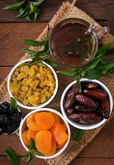 Mix dried fruits (date palm fruits, prunes, dried apricots, raisins) and nuts, and traditional arabic tea. ramadan (ramazan) food. top view