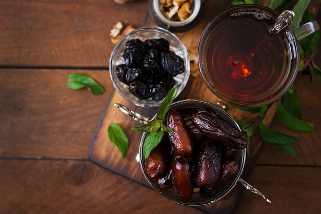 Mix dried fruits (date palm fruits, prunes, dried apricots, raisins) and nuts, and traditional arabic tea. ramadan (ramazan) food. top view