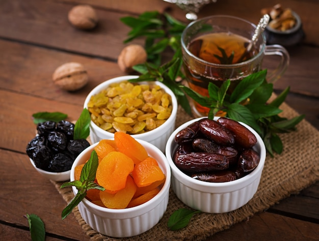 Mix dried fruits (date palm fruits, prunes, dried apricots, raisins) and nuts, and traditional arabic tea. ramadan (ramazan) food. Free Photo