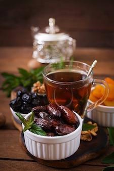 Mix dried fruits (date palm fruits, prunes, dried apricots, raisins) and nuts, and traditional arabic tea. ramadan (ramazan) food.