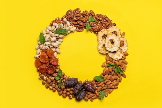 Mix of dried fruits and nuts on a yellow background. top view. symbols of judaic holiday tu bishvat. thanksgiving day. flat lay, top view, copy space