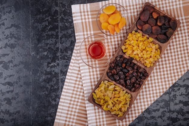 Mix di frutta secca uva passa ciliegie e albicocche su un vassoio di legno servito con armudu bicchiere di tè sulla tovaglia plaid con spazio di copia vista dall'alto