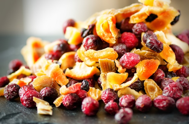 Mix of dried fruits on stone. cranberry, rhubarb, apple, mango, cherry, peach, apricot.
