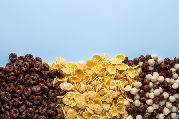 Mix of dry, chocolate balls, rings and yellow corn flakes for cereals breakfast on blue background