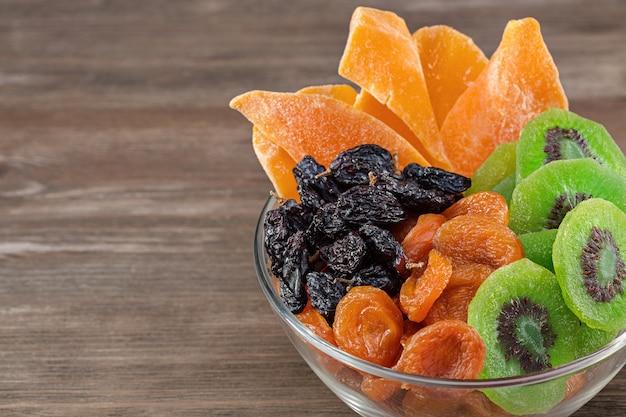Смешайте сухие фрукты на коричневом деревянном фоне.