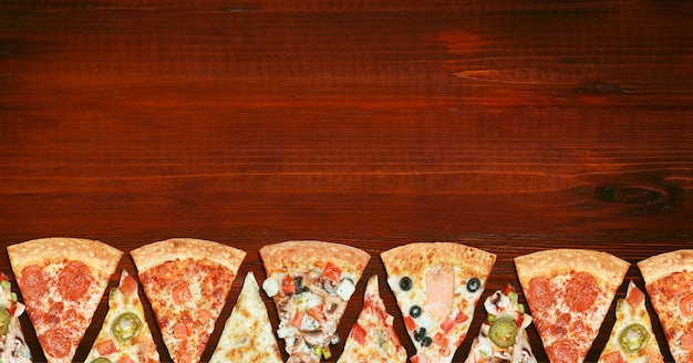 Mix of eight different pizzas on a wooden table  menu concept of choice and diversity