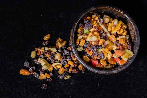 Mix of energetic seeds and dried fruits in a wooden bowl on a black surface. top view