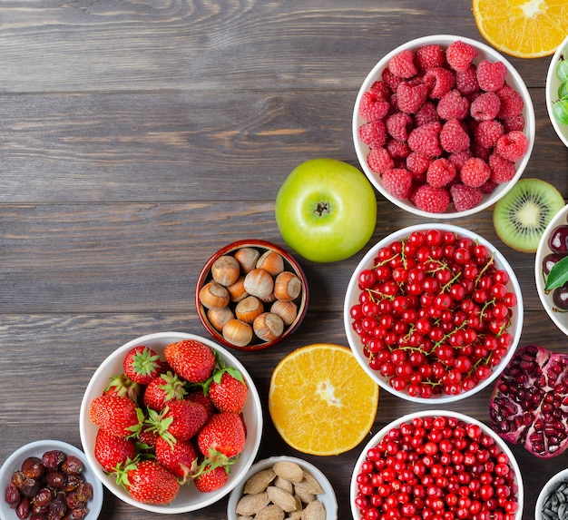 Mix of fresh berries, nuts and fruits on wooden background