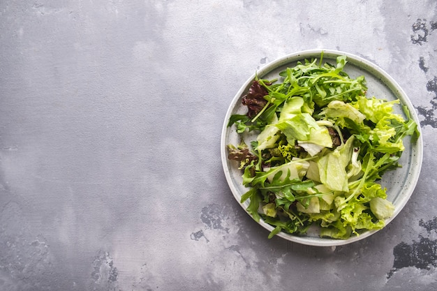 Mix of fresh greens on a plate. fresh summer green salad. top view.