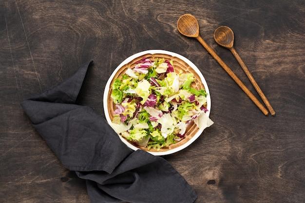 Смешайте свежие листья рукколы, салата, шпината, свеклы для салата в деревянном ящике на деревянном деревенском.