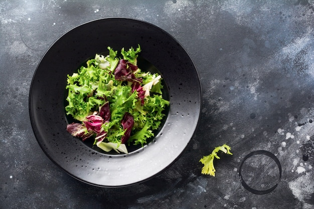 暗い石の背景にルッコラ、レタス、ほうれん草、サラダ用ビートの新鮮な葉を混ぜます。セレクティブフォーカス。