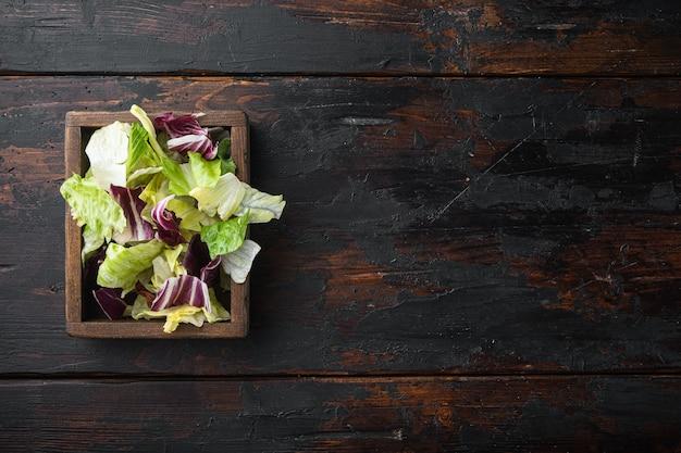 ルッコラ、レタス、ほうれん草、サラダセットのビート、木製の箱、古い暗い木製のテーブル、上面図フラットレイの新鮮な葉を混ぜる