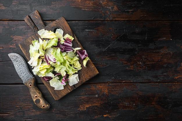 Arugula, 양상추, 시금치, 샐러드 세트 용 사탕무, 나무 커팅 보드, 오래 된 어두운 나무 테이블, 평면도 평면 누워의 신선한 잎을 섞으십시오
