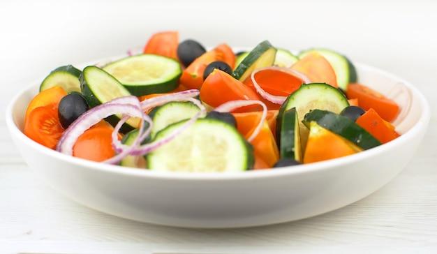 フレッシュサラダにレッドトマト、キュウリ、タマネギ、ブラックオリーブを混ぜる