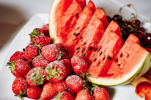Mix of fresh summer fruits and berries on a white plate