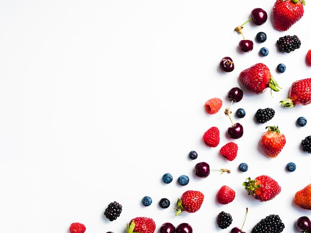 Mix of fresh tasty berries on right of white background
