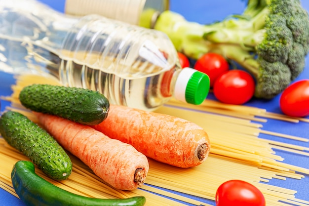 Mix of fresh vegetables, bottles with vegetable oil and sprinkled spaghetti. delivery during the coronavirus pandemic. blue background.