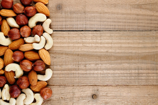 Mix of hazelnuts, almonds and cashew nuts on wood