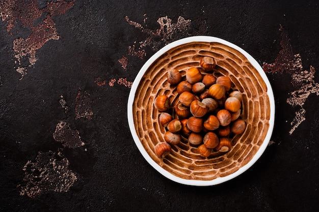 茶色のコンクリート表面のセラミックプレートに健康的な生のヘーゼルナッツとクルミを混ぜます。上面図